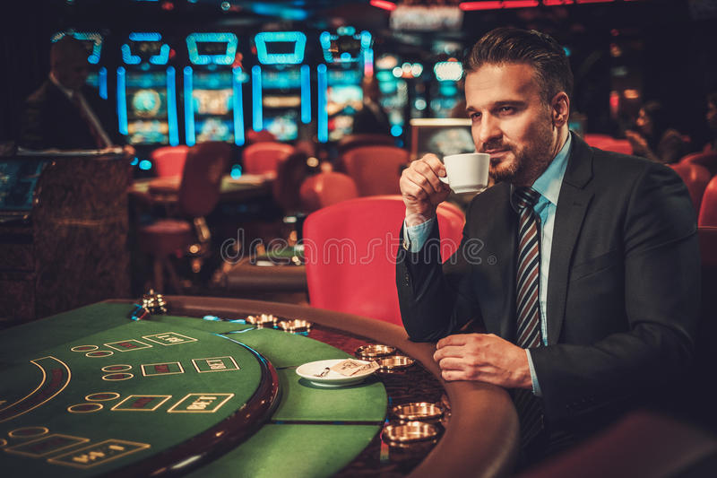 Mann der oberen Klasse hinter Spieltisch in einem Kasino lizenzfreies stockfoto