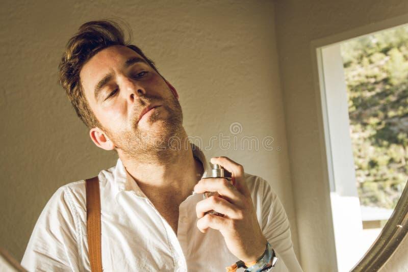 Mann, der Parfüm anwendet Mann, der Cologne anwendet stockfotos