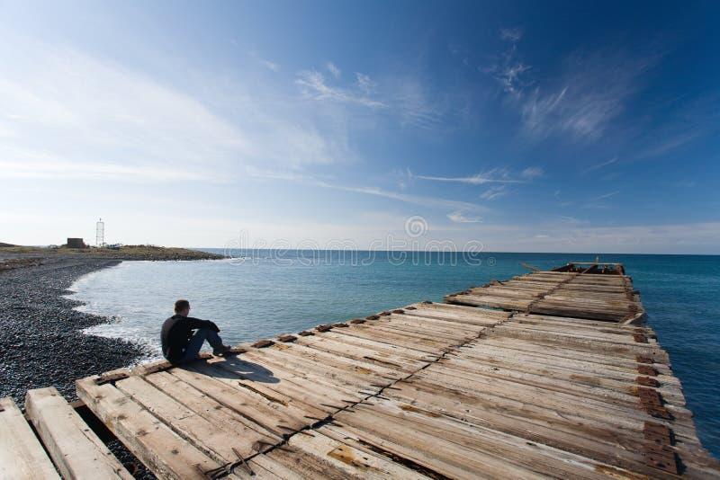 Mann, der am Pier sitzt stockbilder