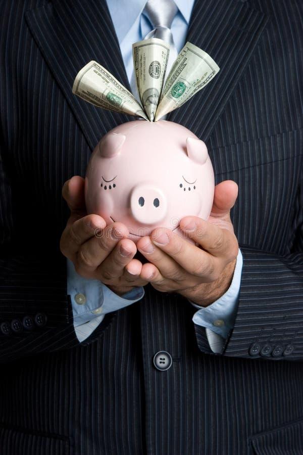 Mann, der Piggy Querneigung anhält lizenzfreie stockfotos