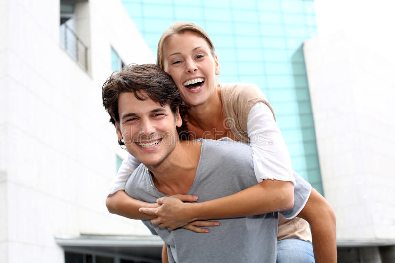 Mann, der piggyback dem Mädchen Fahrt gibt stockbild
