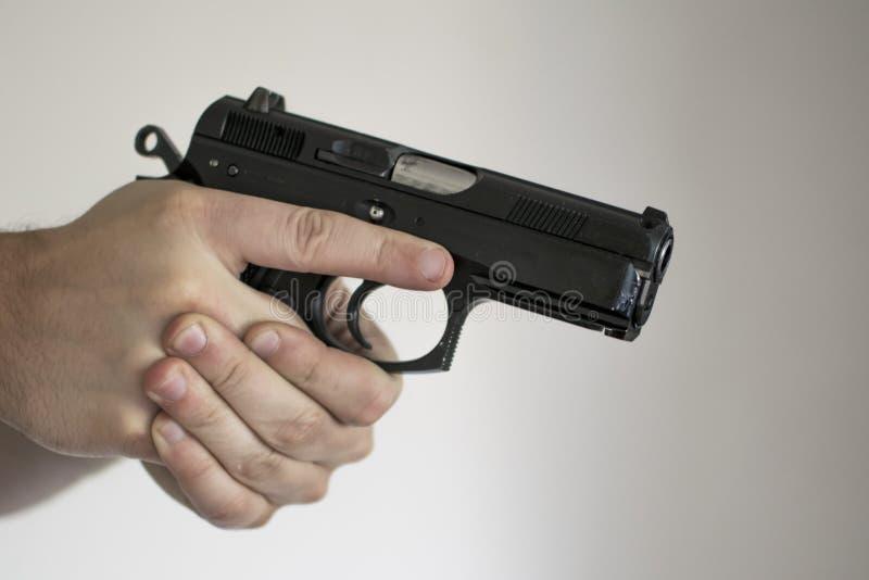 Mann, der Pistole vom Pistolenhalfter in der Selbstverteidigung zielt stockfotos
