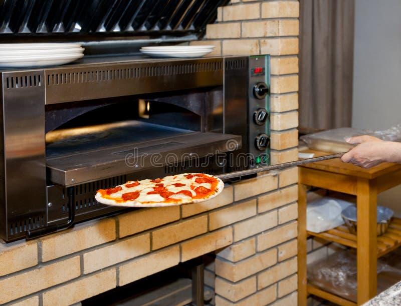 Mann, der Pizza im Ofen einsteckt stockfotografie