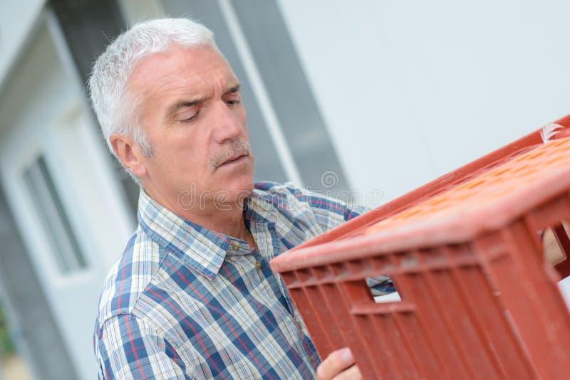Mann, der Plastikkiste trägt lizenzfreie stockfotos