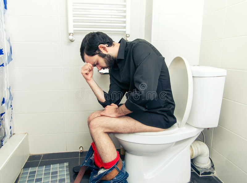 Mann, der Probleme in der Toilette hat lizenzfreies stockbild