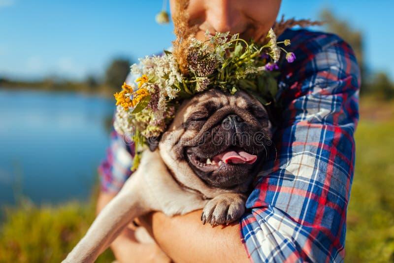 Mann, der Pughund mit Blumenkranz auf Kopf hält Mann, der mit Haustier durch Sommersee geht stockfoto