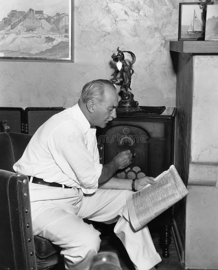 Mann, der Radio hört und Zeitung liest (alle dargestellten Personen sind nicht längeres lebendes und kein Zustand existiert Liefe lizenzfreie stockfotografie