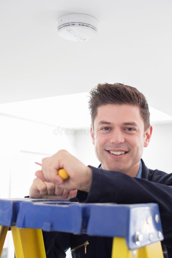 Mann, der Rauch oder Kohlenmonoxid-Detektor installiert stockbild