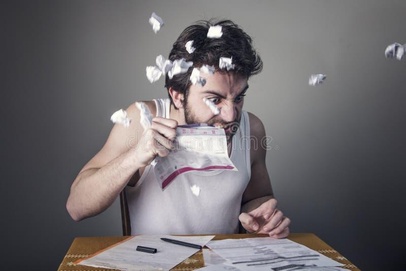 Mann, der Rechnungen auseinander reißt lizenzfreies stockbild