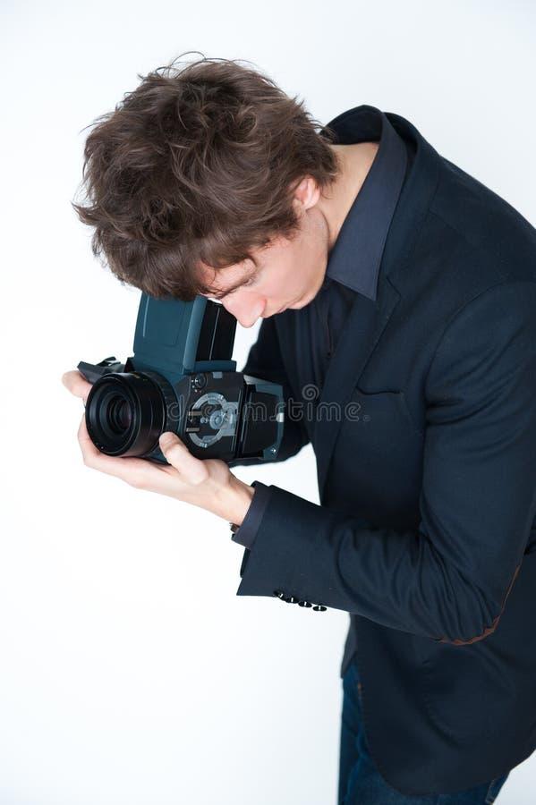Mann, der Retro- Kamera verwendet stockbild