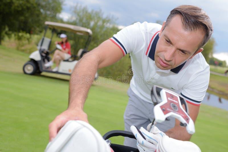 Mann, der in Richtung zu Golf spielender Tasche sich lehnt stockbilder