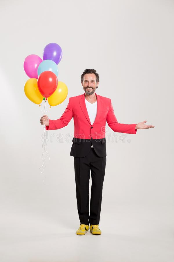Mann in der roten Jacke mit bunten Ballonen lizenzfreie stockfotos