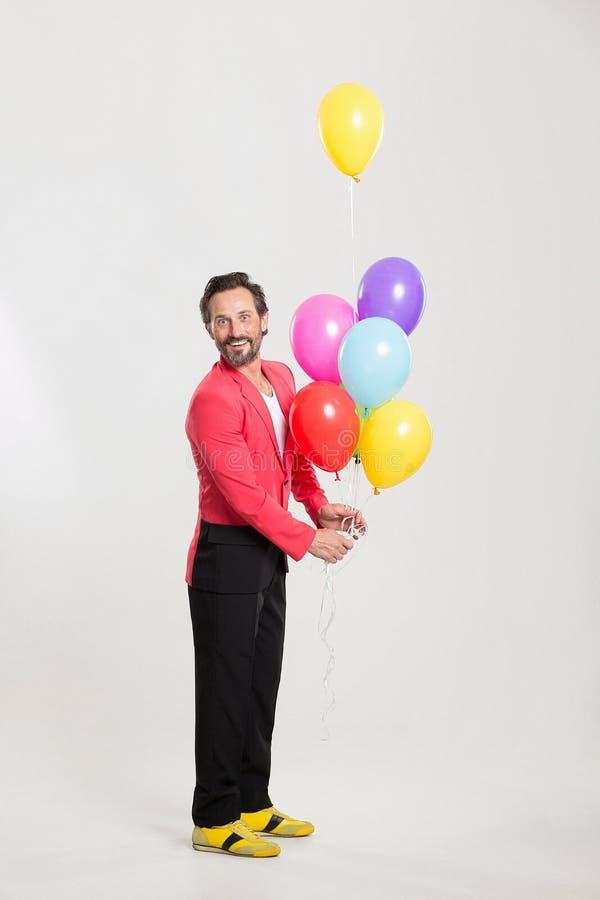 Mann in der roten Jacke mit bunten Ballonen lizenzfreie stockbilder