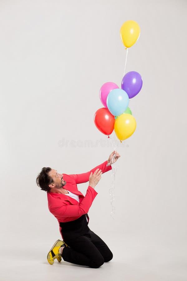 Mann in der roten Jacke mit bunten Ballonen lizenzfreie stockfotografie