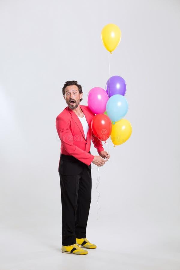 Mann in der roten Jacke mit bunten Ballonen stockfoto