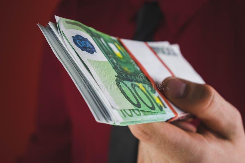 Mann in der roten Klage hält heraus ein Pack des Geldes in seiner Hand auf rotem Hintergrund stockbilder