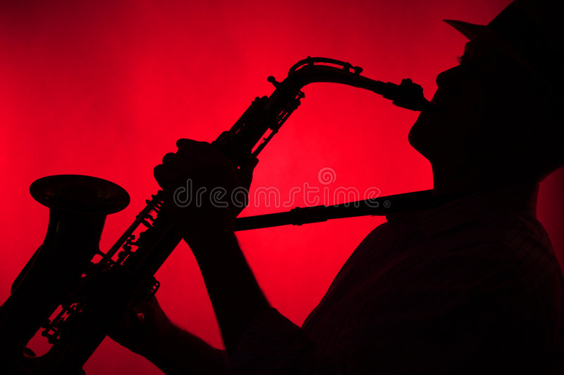 Mann, der Saxophon im Schattenbild spielt lizenzfreie stockbilder