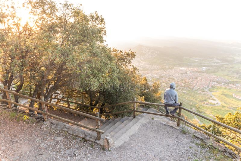 Mann, der schöne Landschaft auf Bank des Berges übersieht stockfotos