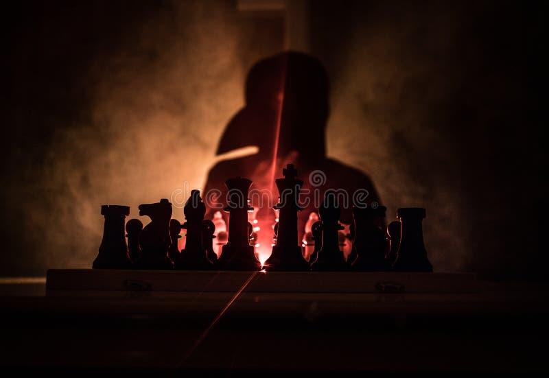 Mann, der Schach spielt Furchtsames unscharfes Schattenbild einer Person am Schachbrett mit Schach stellt dar Dunkler getonter ne lizenzfreies stockfoto
