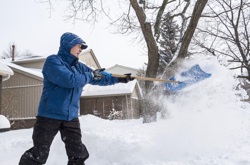 Mann, der Schnee mit einer Schaufel #5 entfernt stockbild
