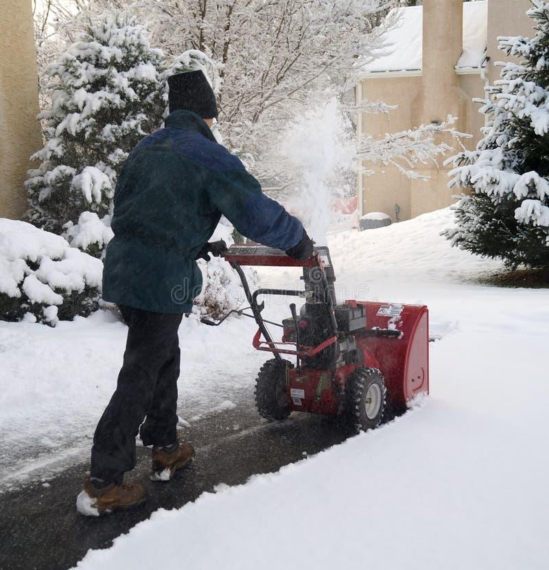 Mann, der Schneefräse während des Winter-Sturms verwendet stockfotografie