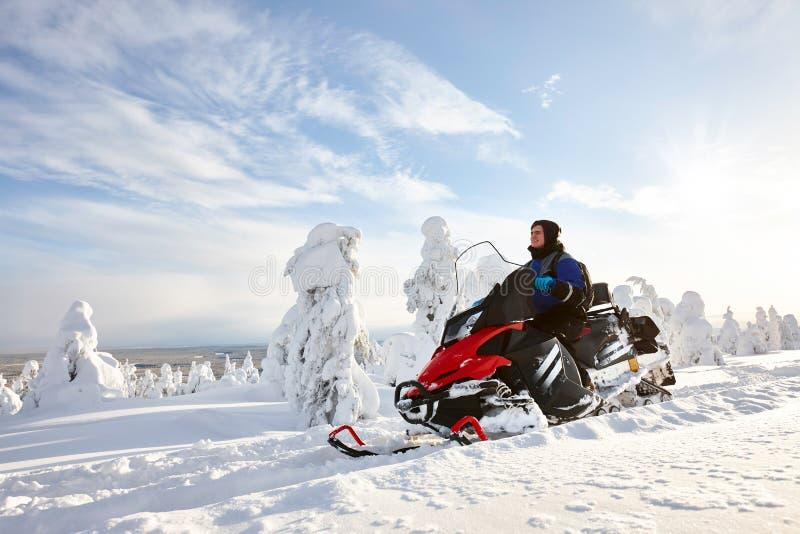 Mann, der Schneemobil fahrung in Finnland fährt lizenzfreie stockfotos