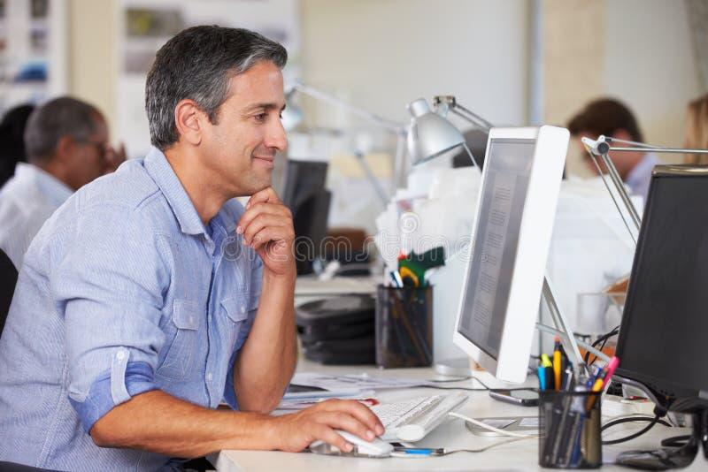 Mann, der am Schreibtisch im besetzten kreativen Büro arbeitet stockfotografie