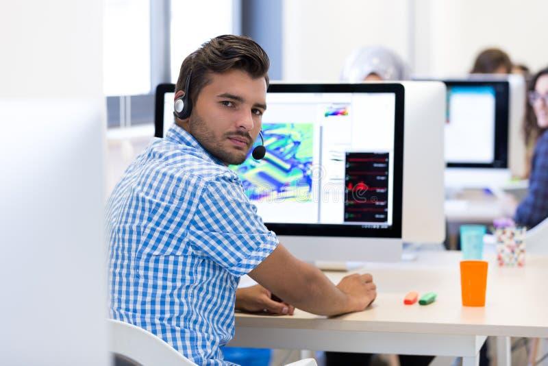 Mann, der am Schreibtisch im besetzten kreativen Büro arbeitet stockfoto