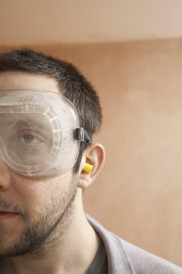 Mann, der Schutzbrillen und Ohrenpfropfen trägt stockbilder
