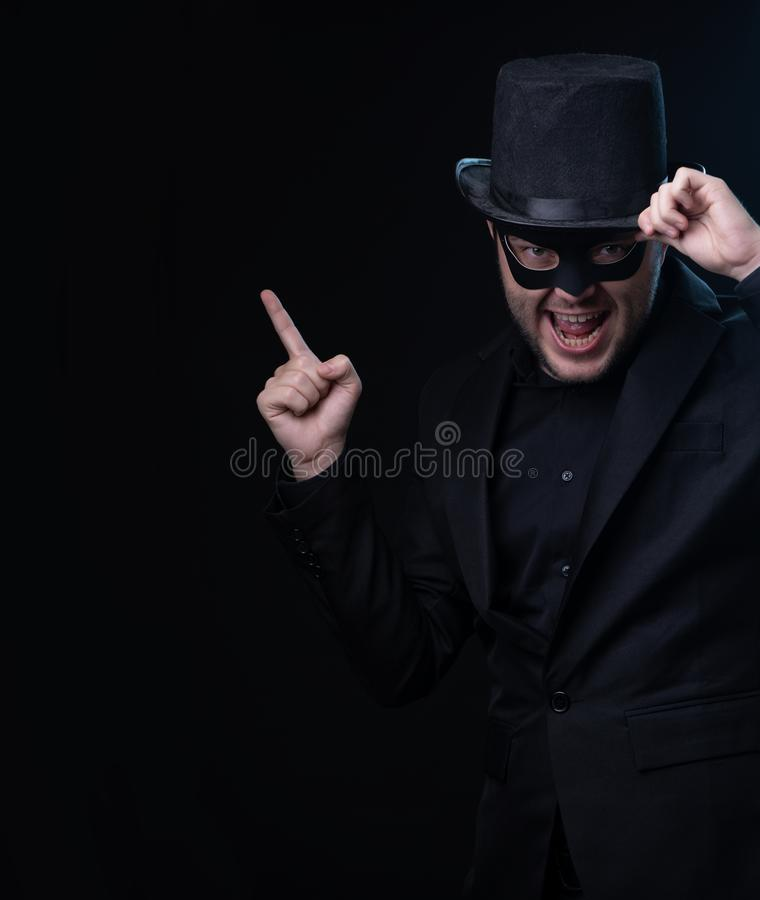 Mann in der schwarzen Maske, Jacke, Hut auf leerem schwarzem Hintergrund lizenzfreie stockfotos