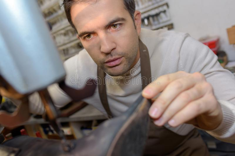 Mann, der schwarzen Schuh repariert stockfoto