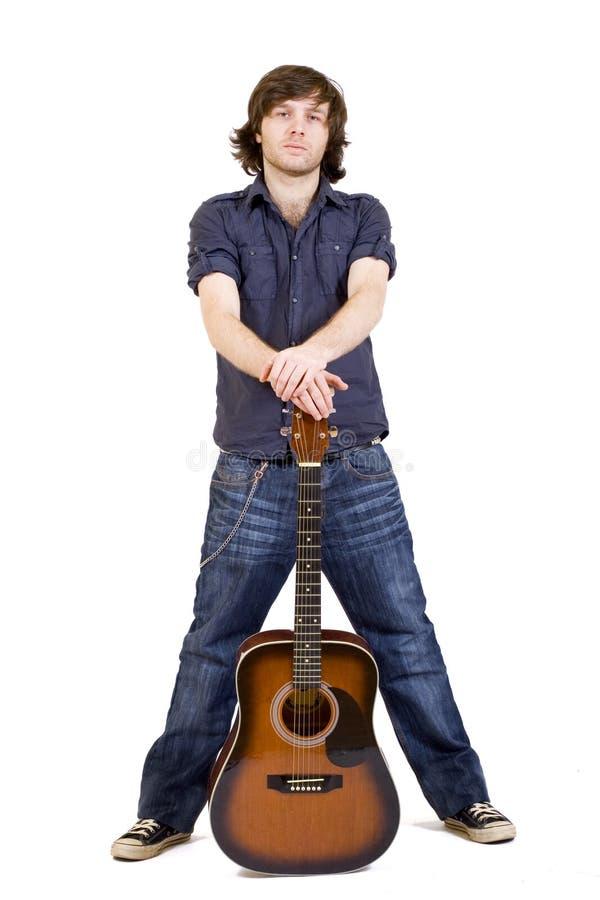 Mann, der seine Akustikgitarre zwischen Fahrwerkbeinen anhält stockbilder