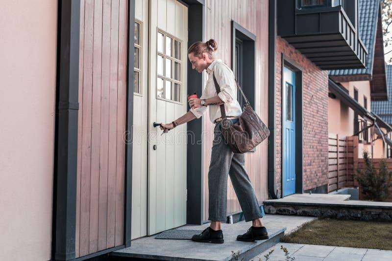 Mann, der seine braune Ledertasche und Kaffee nach Hause zurückkommen trägt stockfoto
