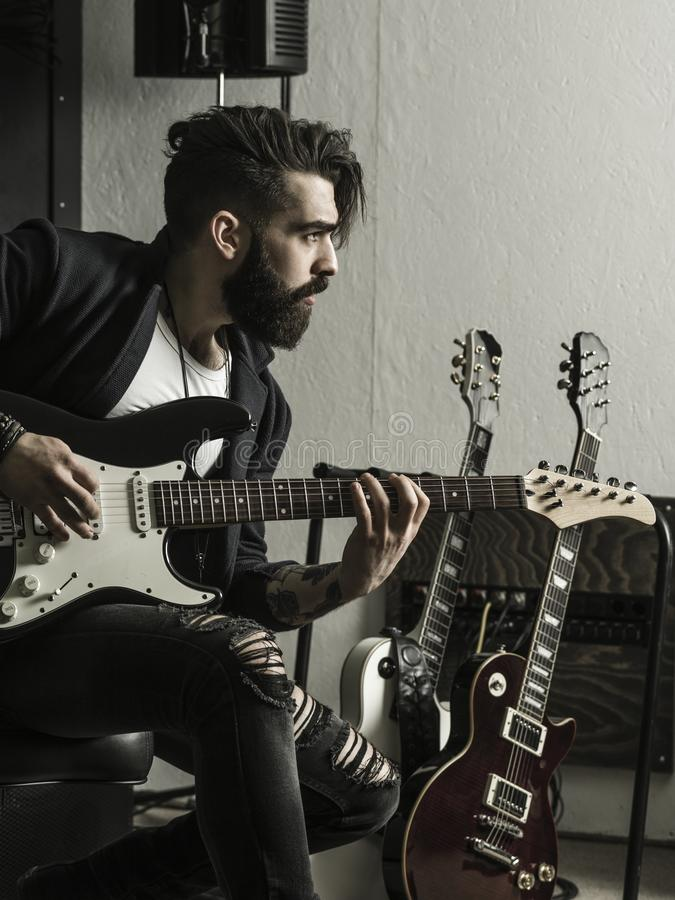 Mann, der seine E-Gitarre in einem Musikstudio spielt stockfoto