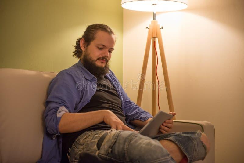 Mann, der seine Ferien in seiner Tablette plant stockbild