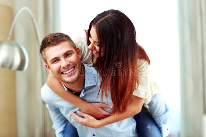 Mann, der seine Frau auf der Rückseite hält lizenzfreie stockfotos