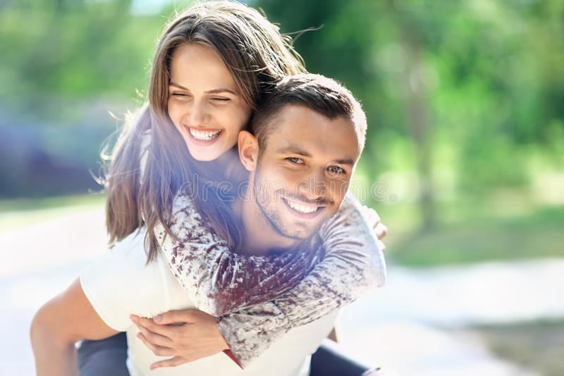 Mann, der seine Freundin auf der Rückseite trägt Glückliche lachende Paare lizenzfreie stockbilder
