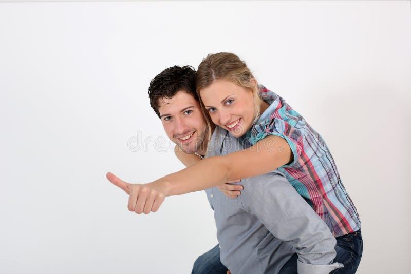 Mann, der seine Freundin auf seinem zurückbringt lizenzfreies stockbild
