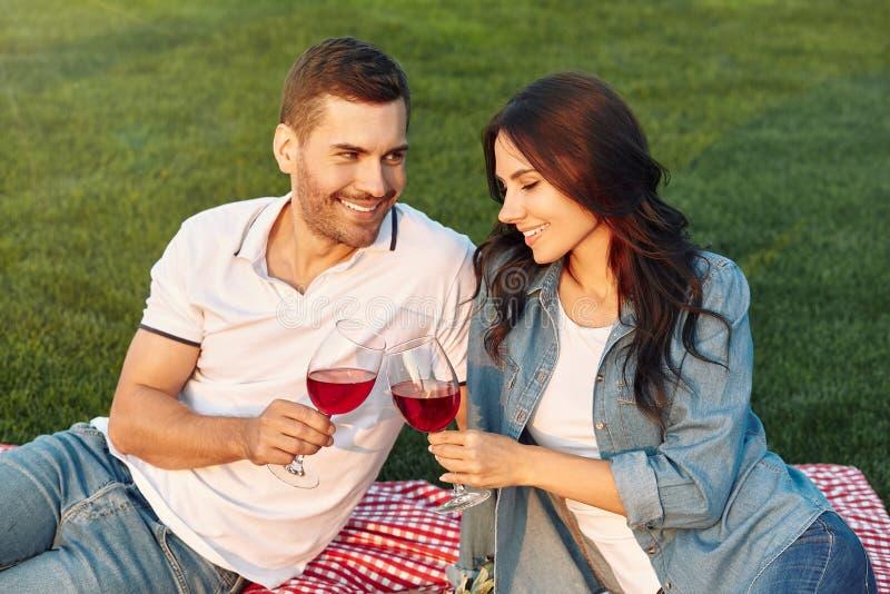 Mann, der seine Freundin betrachtet und Weingläser anklickt stockbilder