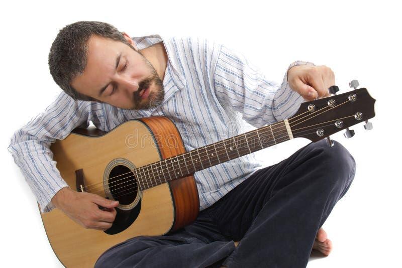 Mann, der seine Gitarre justiert stockbild