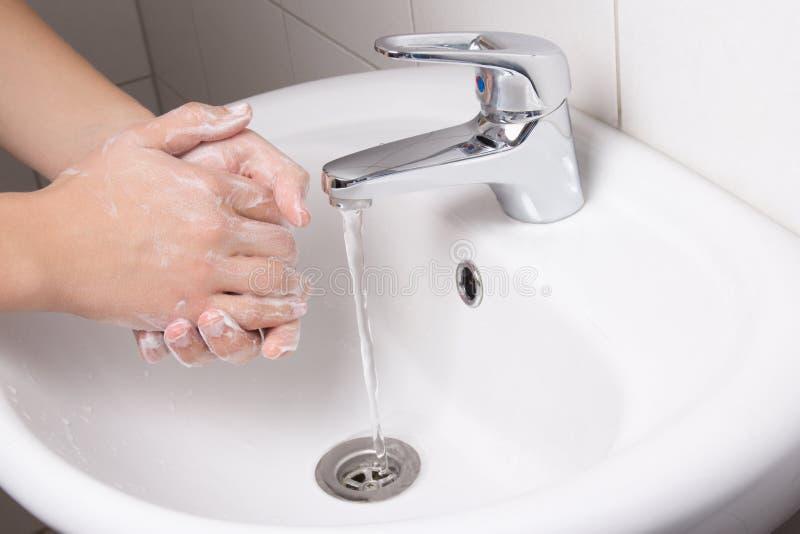 Mann, der seine Hände in der Badezimmerwanne wäscht stockfotografie