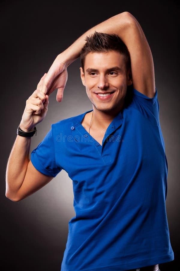 Mann, der seine Hand über seinem Kopf ausdehnt lizenzfreie stockfotos