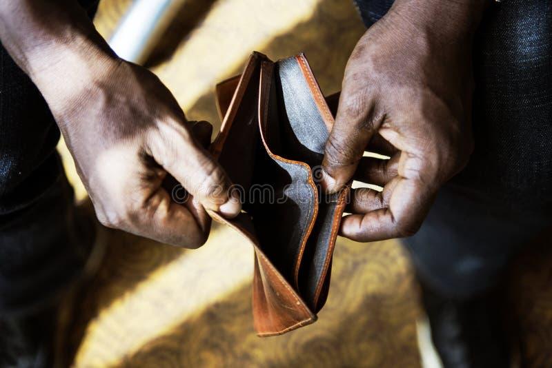 Mann, der seine leere Geldbörse überprüft lizenzfreies stockfoto