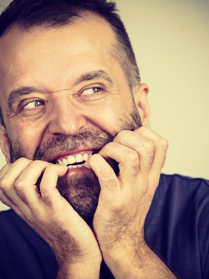 Mann, der seine Nägel beißt stockfotografie
