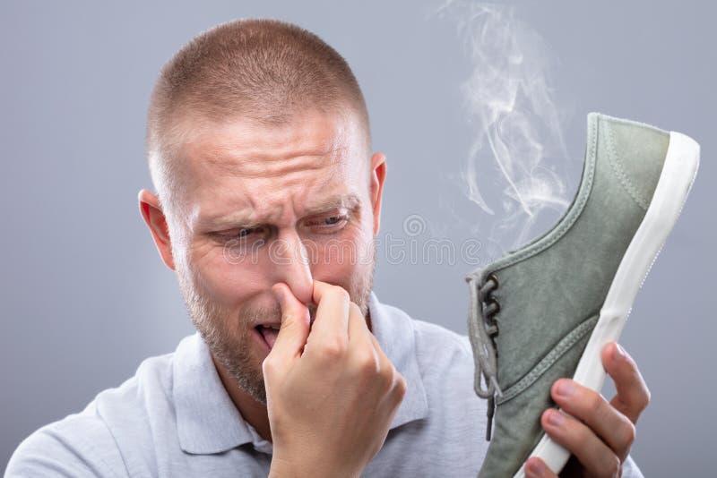 Mann, der seine Nase beim Halten des Stinky Schuhes bedeckt stockfotos