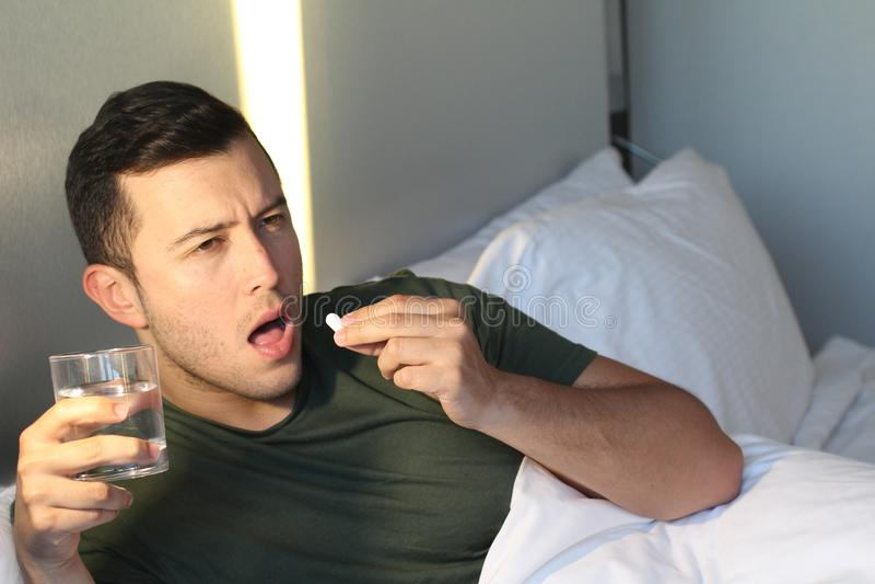 Mann, der seine tägliche Pille einnimmt lizenzfreies stockfoto