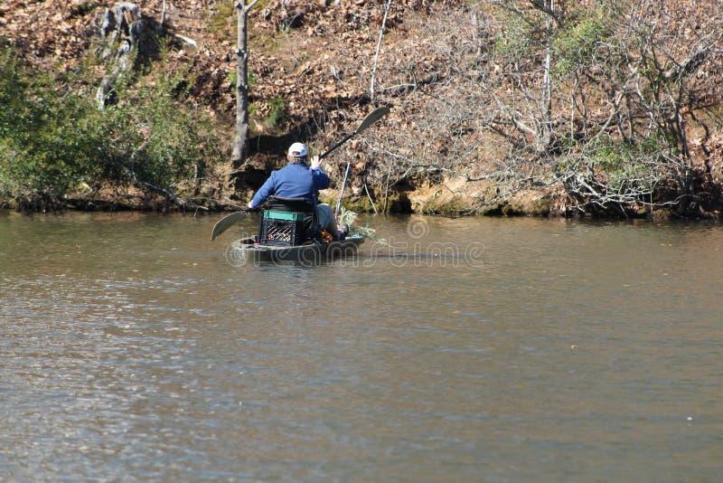 Mann, der in seinem kleinen Boot schaufelt lizenzfreie stockfotografie