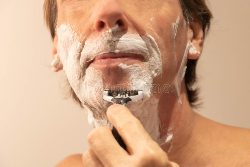 Mann, der seinen Bart mit einem manuellen Rasiermesser rasiert und Schaum rasiert lizenzfreies stockfoto