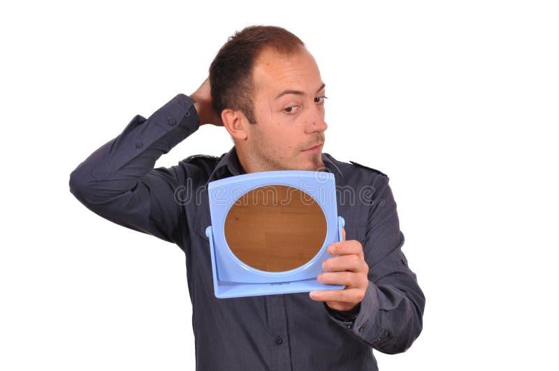 Mann, der seinen Haarausfall im Spiegel überprüft lizenzfreie stockfotografie