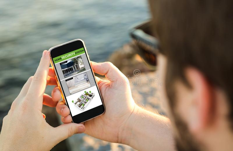 Mann, der seinen Handy auf der Küste zur Überwachung von Webcam verwendet lizenzfreies stockbild